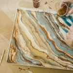 resin art, beautiful overflows of gold, beige and blue paint, golden liquid resin is poured from a plastic cup